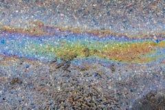 Derramamiento del aceite derramado en el asfalto Imágenes de archivo libres de regalías