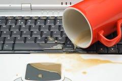 Derramamiento del café en un teclado del ordenador portátil Imagen de archivo