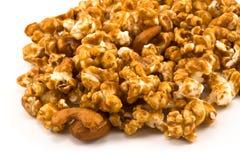 Derramamiento del maíz de oro del caramelo en blanco Foto de archivo libre de regalías