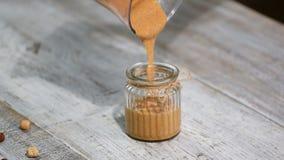Derramando a manteiga da avelã em um frasco vídeos de arquivo