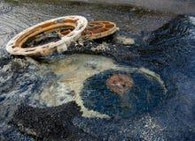Derramando sistemas de fonte da água em um esgoto bem na estrada foto de stock royalty free