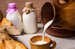 Derramando um copo do leite cremoso fresco imagens de stock