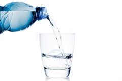 Derramando um vidro com calha da água poucos garrafa e espaço azuis para o texto imagem de stock