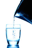 Derramando um vidro da água pura fotografia de stock royalty free