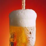 Derramando um vidro da cerveja imagem de stock