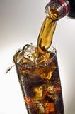 Derramando um vidro da coca-cola com cubos de gelo Imagens de Stock Royalty Free