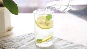 Derramando um vidro da ?gua com lim?o, gelo e hortel? em uma tabela branca video estoque