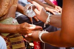 Derrame a água nas mãos de pessoas idosas revered e peça-a Foto de Stock