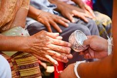 Derrame a água nas mãos de pessoas idosas revered e peça-a Foto de Stock Royalty Free