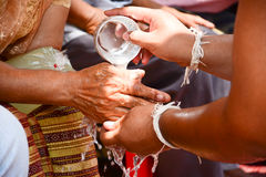 Derrame a água nas mãos de pessoas idosas revered e peça-a Imagem de Stock Royalty Free