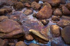Derrame de petróleo Agua y piedras en aceite fotos de archivo