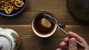 Derrame o açúcar de bastão da colher no copo do chá video estoque