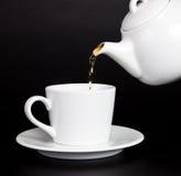 Derrame o chá do teapot no copo fotos de stock