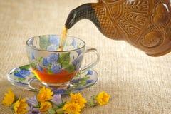 Derrame o chá em uma caneca da chaleira imagens de stock