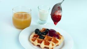 Derrame o doce de morango no waffle caseiro com mirtilo, um vidro do suco de fruto da paixão e leite fresco vídeos de arquivo