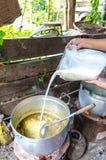 Derrame o leite de coco no potenciômetro do caril. Fotografia de Stock Royalty Free