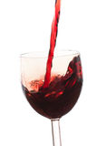 Derrame o vinho no vidro em um fundo branco Imagem de Stock Royalty Free