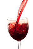 Derrame o vinho no vidro em um fundo branco Imagens de Stock Royalty Free