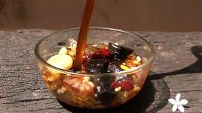 Derrame o xarope no feijão e no cereal sortidos em uma bacia de vidro video estoque