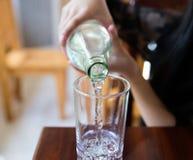 Derrame pouca água em um vidro Fotografia de Stock Royalty Free