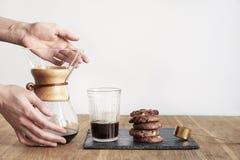 Derrame sobre o método Chemex da fabricação de cerveja do café, posse das mãos da mulher uma bacia de vidro, ainda vida com as co fotografia de stock royalty free