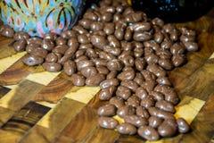 Derramou os feijões com cobertura em chocolate do café dos feijões com fim da caneca de café acima Fotos de Stock Royalty Free