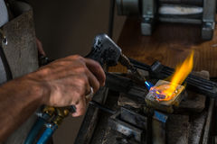 Derretendo um lingote de prata no cadinho com maçarico; imagem de stock royalty free