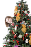 derrière l'arbre de dissimulation de fille de Noël Photos stock