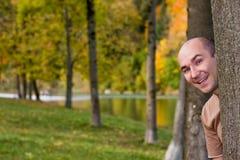 derrière l'arbre de l'homme Images stock