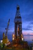 Derrick του γρύλου επάνω στη πλατφόρμα άντλησης πετρελαίου με τον ουρανό λυκόφατος Στοκ Εικόνες