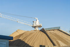 Derrick - crane with heaps of construction material Stock Photos