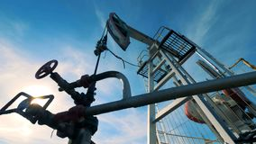 Derrick pumps oil on a special field, bottom view. stock footage