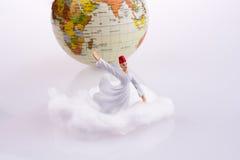 Derviş on a cloud near globe Royalty Free Stock Photo