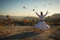 Dervish doing the retual in love valley of Cappadocia with balloons in background at sunrise. royalty free stock images