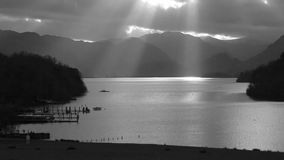 Derwentwater Sunbeams. A black and white timelapse recording of sunbeams shining across Derwentwater in the English Lake District national park stock footage