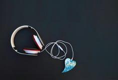 Des écouteurs sont reliés par le câble au coeur Écoutez votre f Photo stock