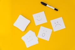 Des émotions dessinées sur les feuilles de papier blanches sont présentées sur un fond jaune Photos stock