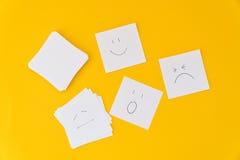 Des émotions dessinées sur les feuilles de papier blanches sont présentées sur un fond jaune Image stock