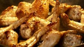 Des ailes de poulet sont faites frire dans une poêle Dîner du poulet L'huile chaude bout dans une poêle clips vidéos