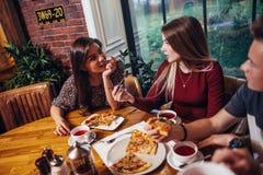 Des amies sont engagées dans une conversation mangeant de la pizza en café Photo stock