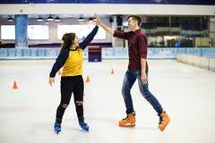 Des amis se donnant de hauts cinq ils sont patinage de glace sur la patinoire Image stock