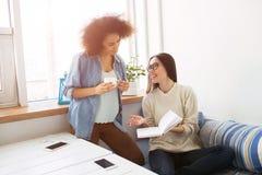 Des amis sont recueillis ensemble dans une chambre L'un d'entre eux se tient avec une tasse de thé et regarde au carnet tandis qu Photo stock