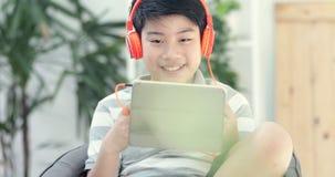Des Asiaten Teenager vor, der zu Hause Tablet-Computer mit Lächelngesicht spielt stock video