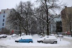 Des automobiles sont couvertes de neige stationnée sur la rue Photos stock