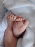 Des Babys geht eingewickelt mit einer Decke auf den Zehen Stockbild