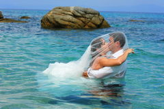 Des baisers de mariée et de marié - trash la robe Images stock