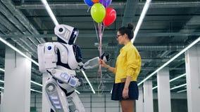 Des ballons colorés sont donnés par une fille à un robot clips vidéos