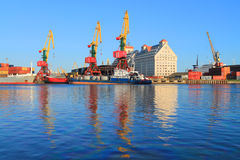 Des bateaux et les grues portailes sont reflétés en rivière Image libre de droits