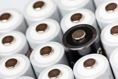 Des batteries d'aa sont situées près de l'un l'autre Plan rapproché de toutes les batteries blanches, excepté une noire, sur un f photographie stock
