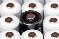 Des batteries d'aa sont situées près de l'un l'autre Plan rapproché de toutes les batteries blanches, excepté une noire, sur un f photos stock